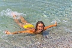 沐浴在清楚的海的美丽的妇女比基尼泳装 免版税库存图片