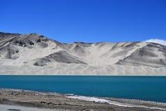 沙丘和土耳其玉色在喀喇昆仑山脉高速公路的,新疆Bulunkou湖浇灌 免版税库存照片