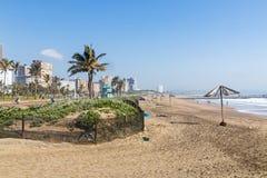 沙丘植被和空的海滩反对城市地平线 库存图片