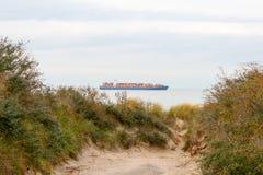 从沙丘看见的容器小船 库存照片