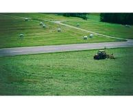 沙伊德格,德国- 2019年6月06日:拖拉机在一个夏日转动在领域的干草 劳斯包装了,新鲜的干燥干草  库存照片