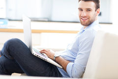 沙发的人有膝上型计算机的 免版税库存图片