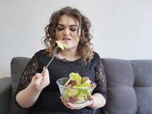 沙发的哀伤的充分的美丽的女孩有不快乐沙拉的饮食的 库存图片