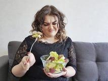 沙发的哀伤的充分的美丽的女孩有沙拉不快乐盘的饮食的 库存照片