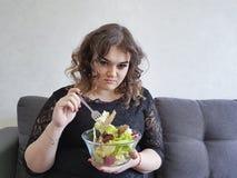 沙发的哀伤的充分的美丽的女孩有沙拉饮食的 图库摄影