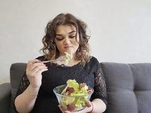 沙发的哀伤的充分的美丽的女孩用沙拉压下了不快乐盘的饮食 免版税库存照片