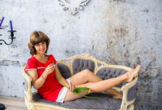 沙发的女孩有一朵红色花的 免版税库存照片