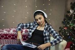 沙发的女孩有在xmas树附近的耳机的 免版税库存照片