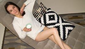 沙发的女孩有杯子的牛奶 免版税图库摄影