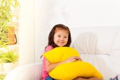 沙发的女孩有枕头的 免版税库存照片
