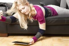 沙发的妇女使用她的片剂个人计算机 免版税库存照片