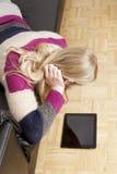 沙发的妇女有片剂个人计算机的 库存图片