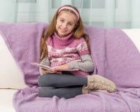 沙发的小女孩有书的 免版税库存照片