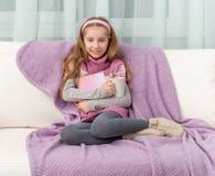 沙发的小女孩有书的 免版税库存图片
