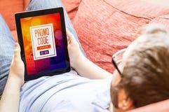 沙发的年轻人有数字式电视节目预告代码的 免版税库存图片
