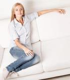 沙发的愉快的少妇 免版税库存照片