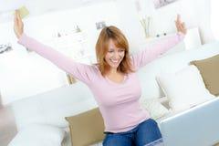 沙发的愉快的激动的妇女有膝上型计算机的 图库摄影