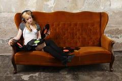 沙发的白肤金发的女孩听到与耳机的音乐的 免版税库存图片