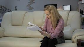 沙发的白肤金发的妇女读她的在笔记本的笔记和与智能手机的检查笔记 影视素材