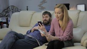沙发的白肤金发的妻子读她的在附近坐和聊天在电话的笔记本和她的丈夫的笔记 股票视频