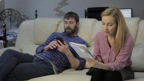 沙发的白肤金发的妻子读她的在附近坐和聊天在电话的笔记本和她的丈夫的笔记 股票录像