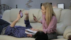 沙发的白肤金发的妻子读她的在附近说谎和聊天在电话的笔记本和她的丈夫的笔记 股票视频
