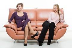 沙发的美丽的女性朋友 两 免版税库存图片