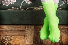 从沙发的脚突出物在绿色袜子 免版税图库摄影