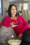 沙发的西班牙妇女观看电视吃Popcron的 图库摄影