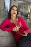 沙发的西班牙妇女观看电视饮用的酒的 免版税库存图片