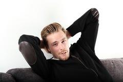 沙发的年轻和轻松的人 免版税库存图片