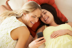 沙发读取正文消息的二个女性朋友 免版税库存照片