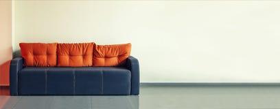 沙发,室内设计,办公室 倒空有一个现代蓝色沙发的候诊室有在门和时钟前面的黄色坐垫的  免版税库存图片