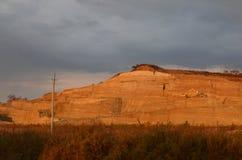 沙坑的看法与挖掘机和卡车的在距离 免版税库存图片