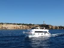 沙姆沙伊赫,埃及- 2009年12月29日:沿岩石的白色小船航行在红海 库存图片