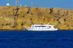 沙姆沙伊赫,埃及- 2018 3月14日,豪华白色马达游艇在反对老珊瑚礁蓝天的红海  免版税库存图片