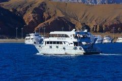 沙姆沙伊赫,埃及- 2018 3月14日,豪华白色马达游艇在反对老珊瑚礁蓝天的红海  免版税库存照片