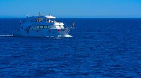 沙姆沙伊赫,埃及- 2018 3月14日,豪华白色马达游艇在反对老珊瑚礁蓝天的红海  图库摄影