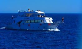 沙姆沙伊赫,埃及- 2018 3月14日,豪华白色马达游艇在反对老珊瑚礁蓝天的红海  库存图片