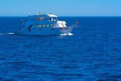 沙姆沙伊赫,埃及- 2018 3月14日,豪华白色马达游艇在反对老珊瑚礁蓝天的红海  库存照片