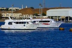 沙姆沙伊赫,埃及- 2018 3月14日,豪华白色马达游艇在反对老珊瑚礁蓝天的红海  免版税图库摄影