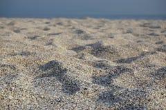 沙子和小卵石特写镜头视图在海滩与海背景的 免版税图库摄影
