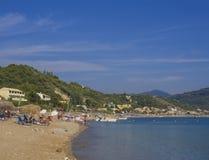 沙子和小卵石baech和绿松石在贴水科孚岛海岛的,希腊乔治斯Pagon的海岸有在波尔图timony海湾的看法 免版税库存照片
