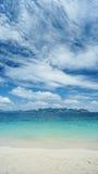 沙子和海蓝天和云彩的在阳光下 免版税图库摄影