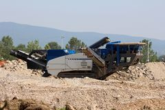 沙子和石流动冲击式破碎机植物停放在地方工地工作等待的卡车 免版税库存图片