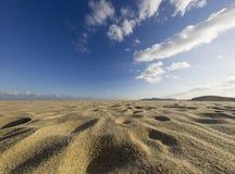 沙子和蓝色多云天空 库存照片