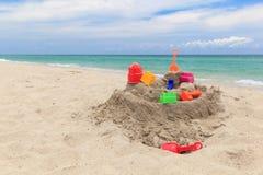 沙子城堡和孩子玩具在海滩 免版税库存照片
