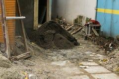 黑沙子堆在一个房子的整修项目的在德波拍的一张白色砖墙照片附近的雅加达印度尼西亚 库存图片
