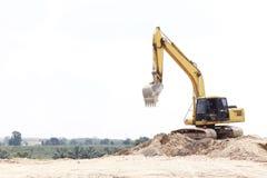 在沙子堆的挖掘机 库存照片