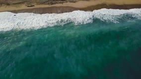 沙子海滩 股票 一个美丽的沙滩的顶视图与蓝色的挥动辗压入岸 背景峡湾光芒海运星期日 库存照片